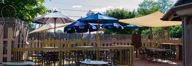 An outdoor deck attached to the zia maria restaurent with tables and umbrellas for shade.
